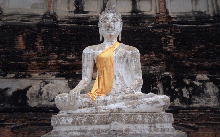 Будда на фоне древней стены